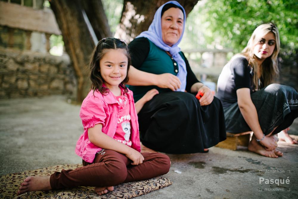 Une fillette yézidi en compagnie de ses proches qui discutent à l'ombre des arbres sacrés du temple.