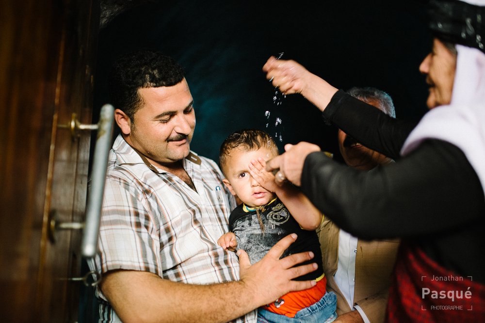 L'eau de la source blanche du temple de Lalesh est versée sur un jeune yézidi pour le baptiser.